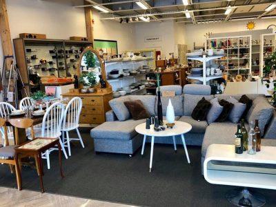 En grå soffa, två vita soffbord. Matbord och vita stolar. Byrå i trä. I bakgrunden hyllor fyllda med varor till salu.