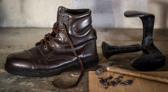 Brun sko står på en träbänk, en hammare ligger bredvid för att laga skon.