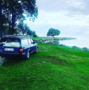 En blå Volvo som står parkerad vid vatten, grönskande omgivning