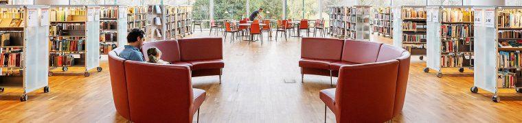 Några röda stolar i ett bibliotek med bokhyllor