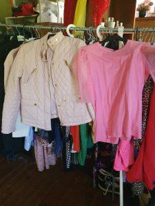 Rosa blus och vit jacka hängandes på ett klädställ