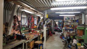Verkstad, på väggarna hänger verktyg, längst in står några mopeder